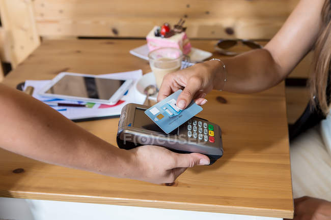 Crop hands paying with wireless credit card in cafe — Stock Photo