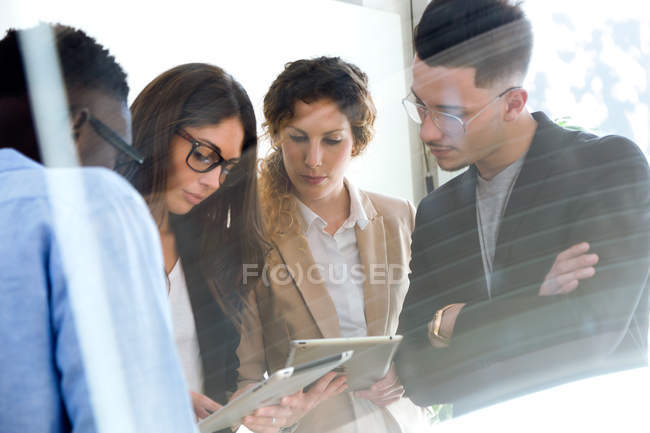 Group of business people looking at tablet in hands of colleague while meeting in modern office. — Stock Photo