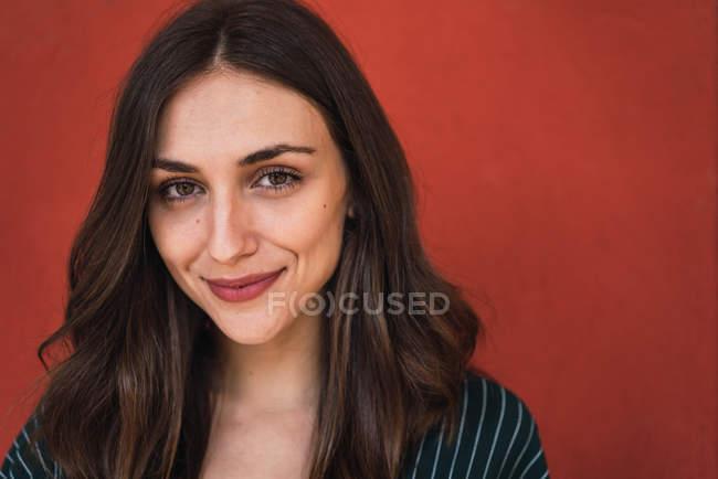Портрет улыбающейся брюнетки в полосатом платье, позирующей на красном фоне и смотрящей в камеру — стоковое фото