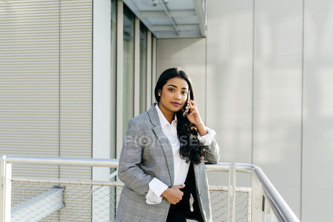 Вдумчивый предприниматель в куртке, опираясь на перила и говоря телефон на балкон — стоковое фото