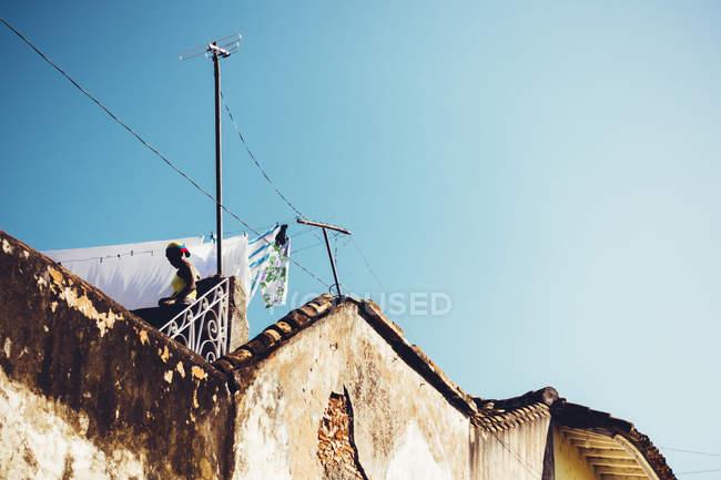 Cuba - 27 de agosto de 2016: Alto ángulo exterior vista de fachada y hombre sobre cielo azul - foto de stock