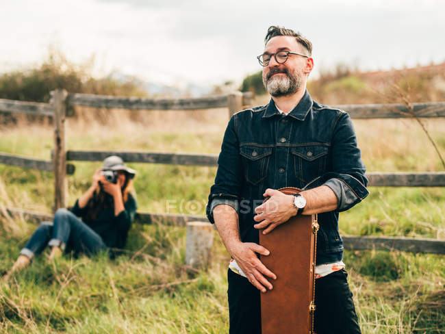 Woman with vintage camera leaning on rural fence at countryside and taking shot of man cheerfully posing with guitar case and looking at camera — Stock Photo