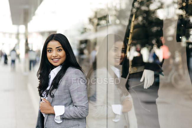Elegant businessoman posing near shop window and looking at camera — Stock Photo