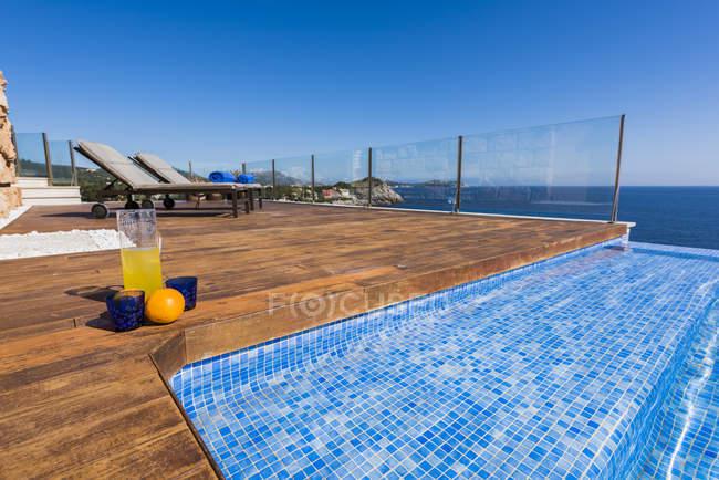 Vista exterior de terraza de madera con camas lounge y azul agua de piscina en el fondo - foto de stock