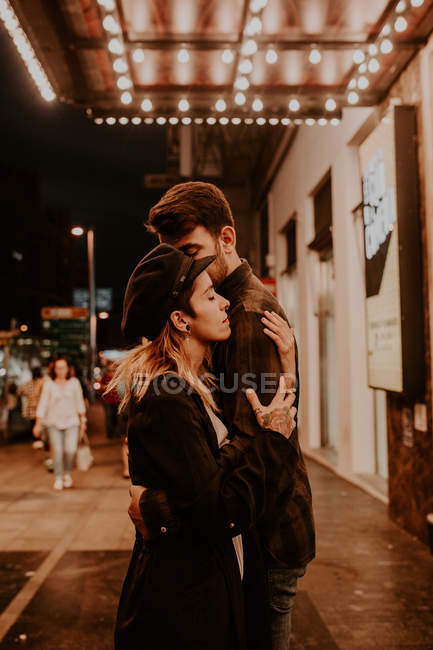 Seitenansicht eines Pärchens, das sich auf der Abendstraße sinnlich umarmt — Stockfoto