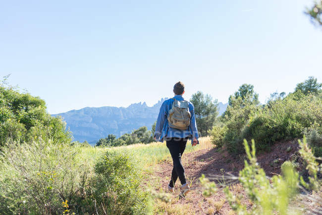 Rear view of man with backpack walking on nature — Stock Photo