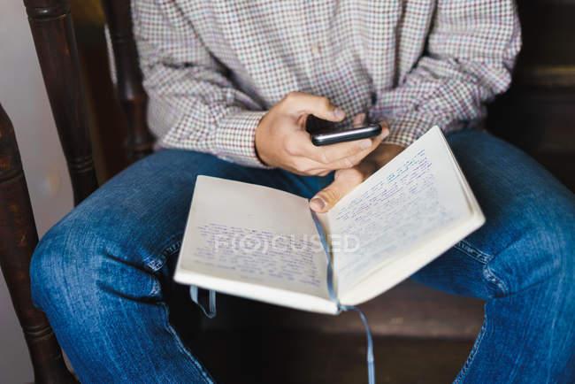 Средняя секция человека сидит на лестнице с ноутбуком и просматривает смартфон — стоковое фото