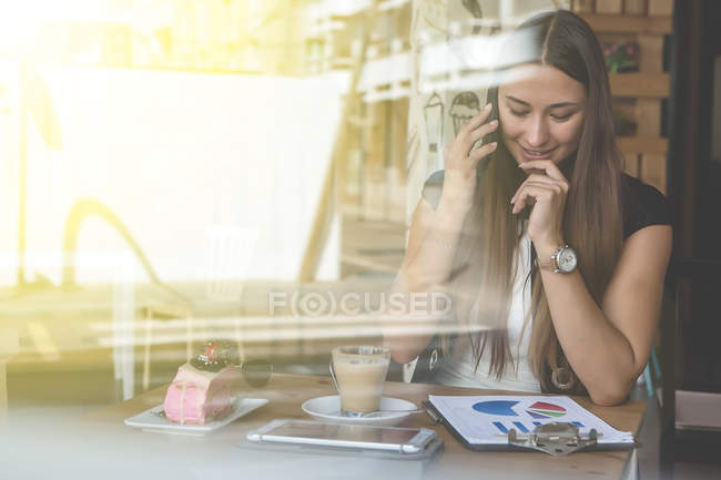 View through window od woman working in cafe and having coffee — Stock Photo