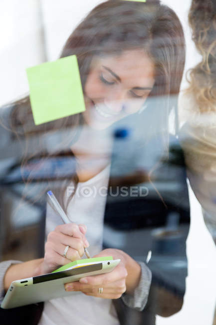 Portrait of young businesswoman holding tablet and making note on sticker — Stock Photo