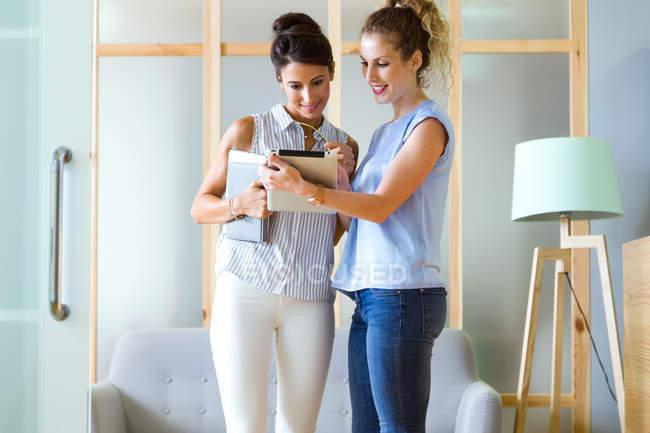 Портрет бизнес женщина показаны планшетного экрана, чтобы коллеги в офисе коридор — стоковое фото