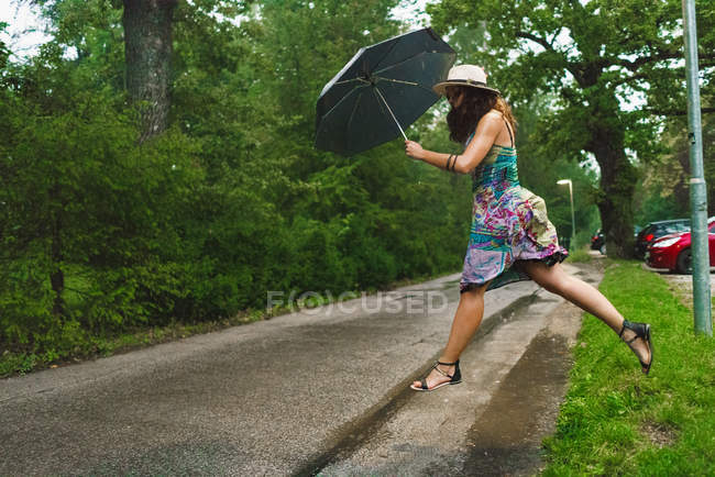 Side view of woman with umbrella jumping over paddle on road — Stock Photo