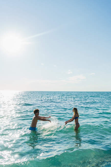 Side view of couple having fun in ocean water — Stock Photo