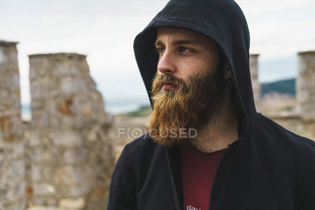 Portrait of bearded man in hood looking away — Stock Photo