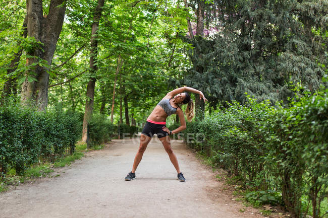 Girl stretching aside on park alley before workout — Stock Photo