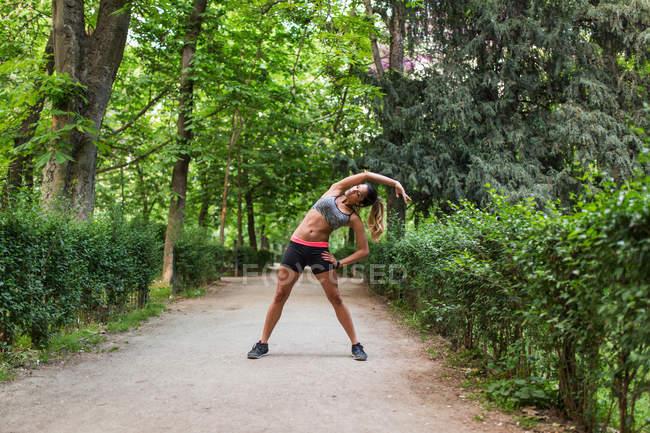 Menina, estendendo-se de lado no beco do parque antes de treino — Fotografia de Stock