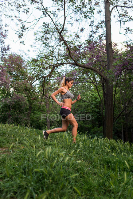 Jeune fille jogging bas de la colline au parc — Photo de stock