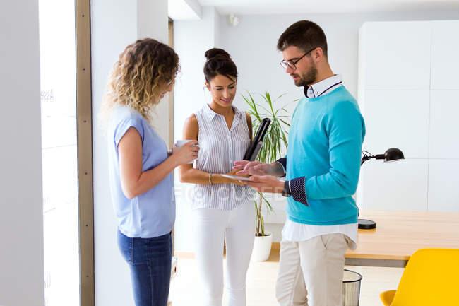 Портрет предпринимателя показаны планшетного экрана коллегам в современном офисе. — стоковое фото