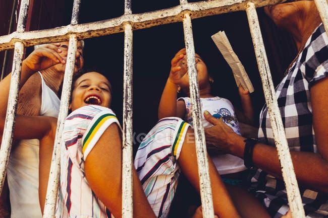 Куби - 27 серпня 2016: Веселий дітей і дорослих, стоячи за металевими гратами на вулиці сцени — стокове фото