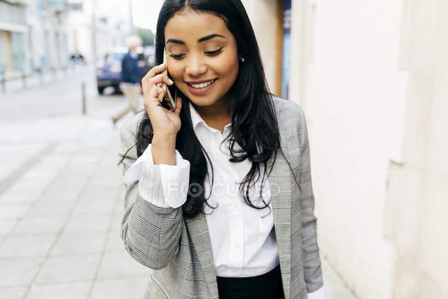 Портрет элегантной деловой женщины, разговаривающей по телефону на улице — стоковое фото