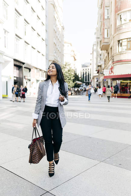Elegant woman with handbag walking on street and looking aside — Stock Photo