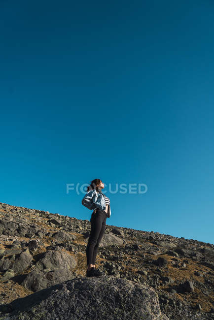 Low angle view of woman standing on rocky slope — Stock Photo