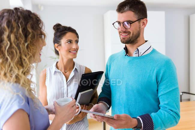 Lächelnde Gruppe von Geschäftsleuten, die in modernen Büro miteinander zu reden — Stockfoto