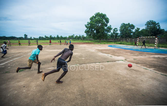 BENIN, AFRICA - AUGUST 31, 2017: Group of boys playing football on concrete field . — Stock Photo