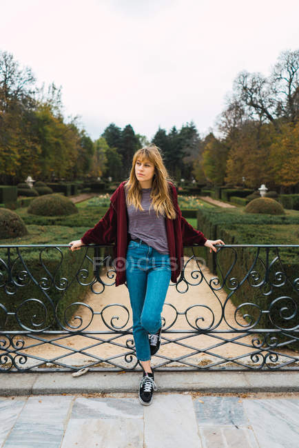 Young casual model leaning on fence in beautiful garden and looking away pensively. — Stock Photo