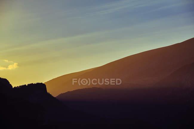 Пастельні силуети гір над захід сонця небо — стокове фото