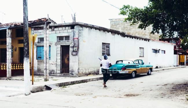 Куба - 27 августа 2016: Вид сзади женщину ходить в бедных городских улиц с ветхих зданий — стоковое фото