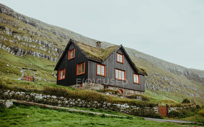 Low angle view of wooden house on rocky highlands slope — Stock Photo