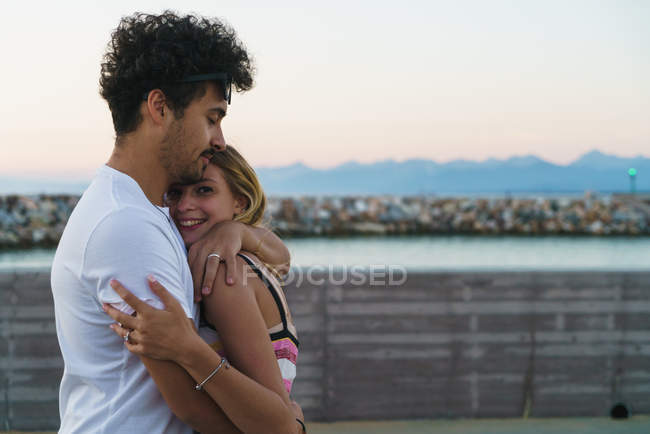Side view of man embracing girlfriend on pier — Stock Photo