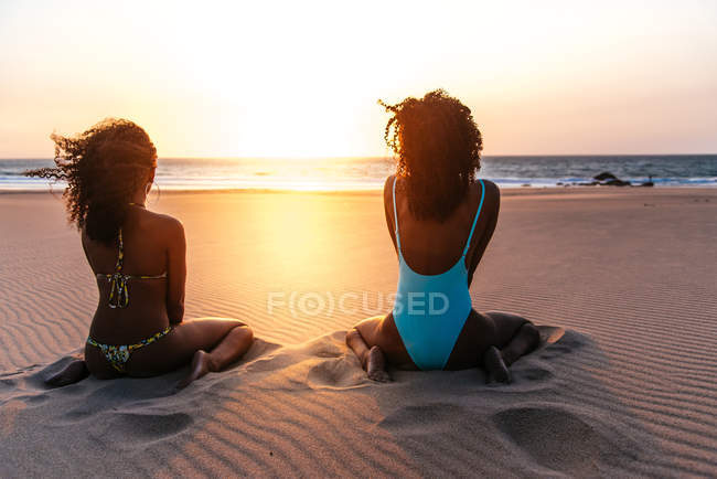 Rear view of women sitting on tropical beach and admiring sunset seascape — Stock Photo