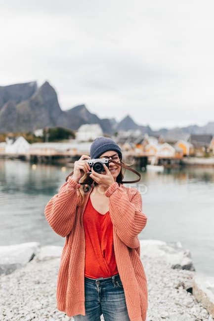 Mujer en punto cárdigan y sombrero tomando fotos en la cámara analógica en el lago de montaña . - foto de stock