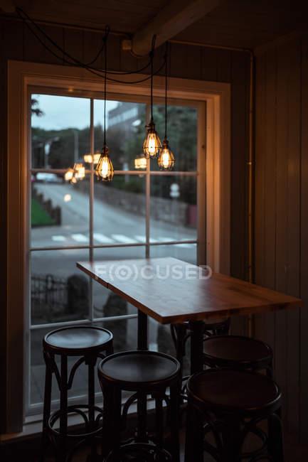 Taburetes de bar y mesa de madera junto a la ventana - foto de stock