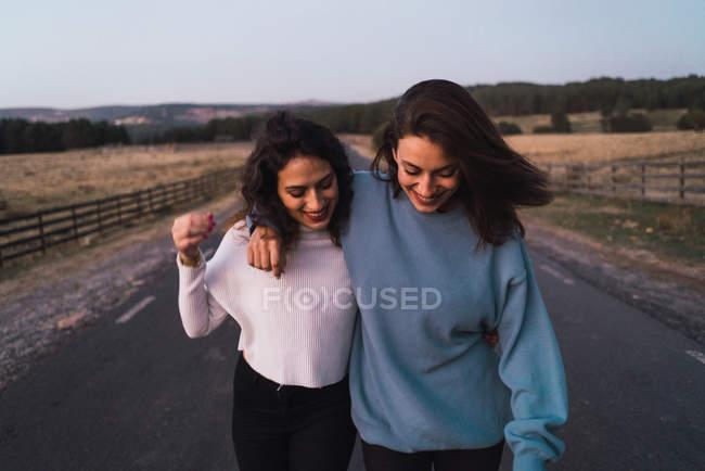 Retrato de abraçar as meninas andando ao longo de estradas rurais — Fotografia de Stock