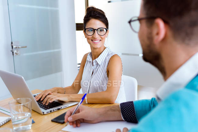 Portrait of smiling  businesswoman looking at colleague in modern office — Stock Photo