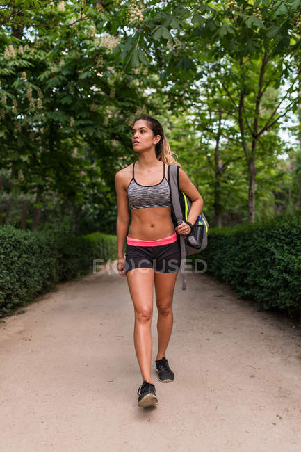 Menina em sportswear carregando mochila e andando no beco do parque — Fotografia de Stock