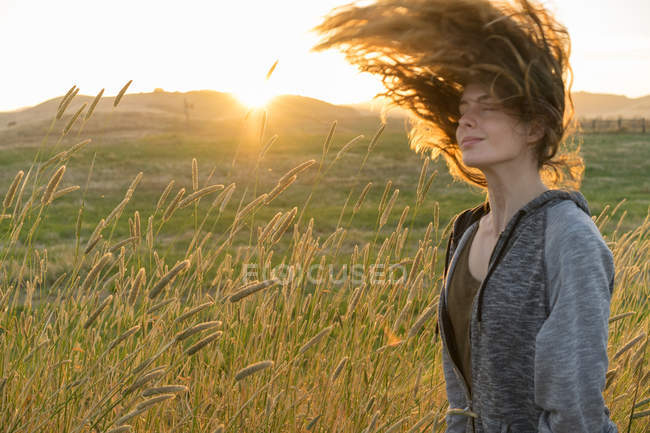 Side view of woman with eyes closed shaking hair in wheat field at sunset — Stock Photo