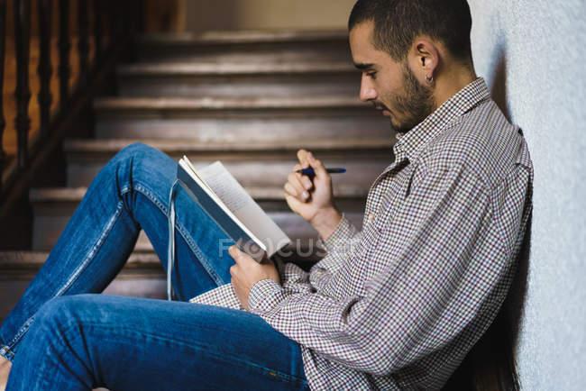 Вид сбоку на юного студента в клетчатой рубашке, сидящего на лестнице и пишущего в блокноте . — стоковое фото