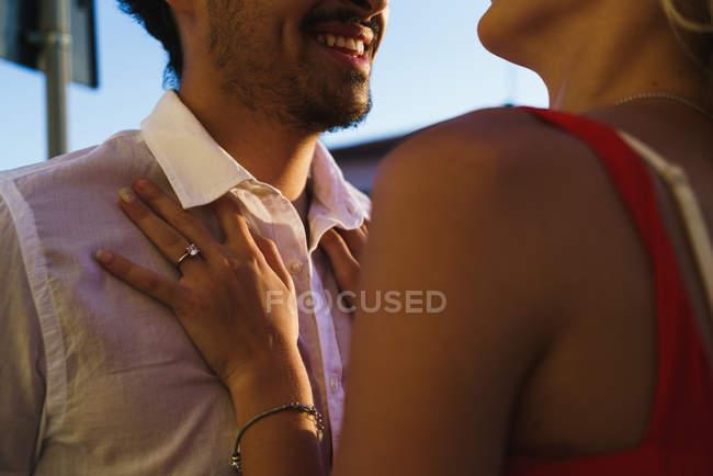 Cultivo de jóvenes amantes de la pareja abrazándose y riendo en la luz del sol. - foto de stock