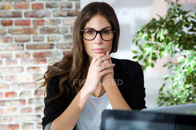 Portrait of young thoughtful businesswoman looking at camera. — Stock Photo