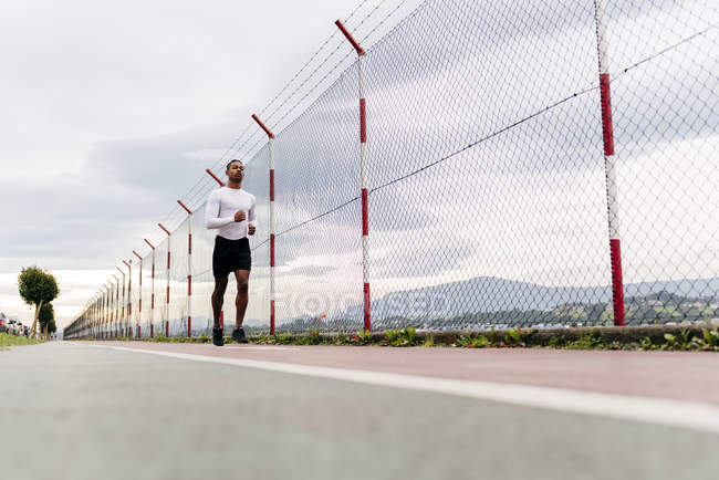 Surface view of athlete running along fence — Stock Photo