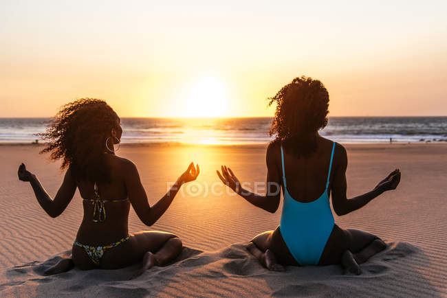 Rear view of women sitting in yoga asana on tropical beach and meditating over sunset sky on background — Stock Photo