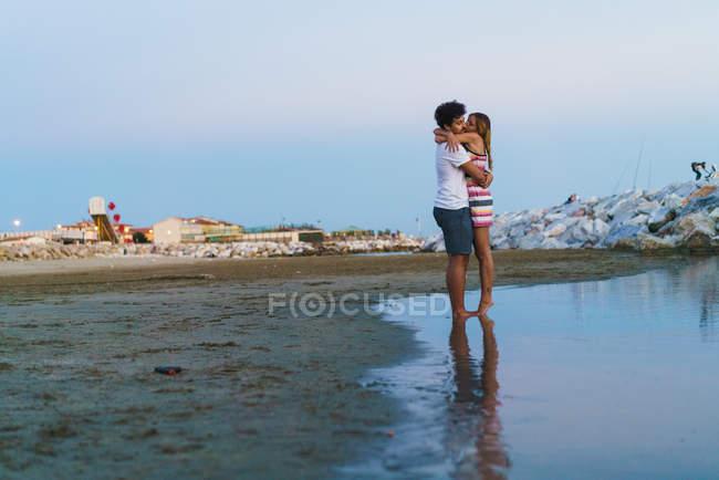 Vue latérale lointaine d'un couple aimant embrassant sur la plage — Photo de stock