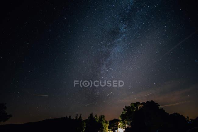 Vista panorâmica para a zona rural de noite e a Via Láctea no céu — Fotografia de Stock