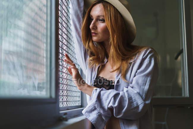Donna rossa in cappello posa alla finestra con persiane — Foto stock