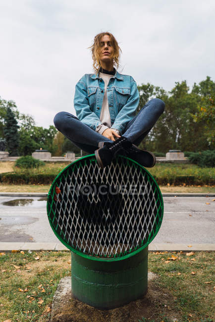 Young woman in sitting with legs crossed on ventilation tube at park — Stock Photo