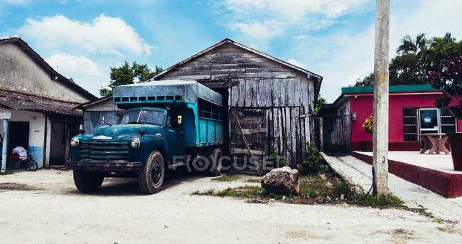 Куба - 27 августа 2016: Blue старый грузовик, на стоянке под крышей деревянных выветривания гараж на улице — стоковое фото