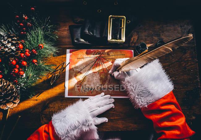 Выше мнению Санта Клаус руки рисунок с перо подарок доставки маршруты на карте мира — стоковое фото